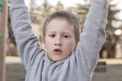 Portret van leuke jonge jongen die de camera op kinderenspeelplaats bekijken Pre-school kind die pret op speelplaats hebben Jong  stock fotografie