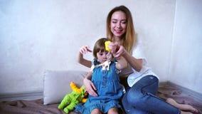 Portret van leuke jonge moeder en meisjedochter, die samen pret in heldere ruimte in dag hebben stock video