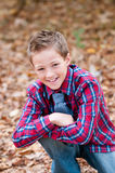 Portret van leuke jongenszitting in bladeren met één knie royalty-vrije stock foto