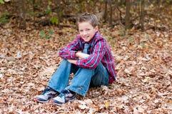 Portret van leuke jongenszitting in bladeren met gekruiste benen stock afbeelding