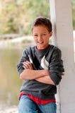 Portret van leuke jongenszitting in gazebo met gekruiste handen stock afbeelding