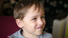 Portret van leuke kleine het kijken beeldverhalen en het glimlachen Kinderen` s emoties stock video