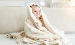 Portret van leuke 10 maanden oud die de zitting van de babyjongen op bed glimlachen onder grote deken Royalty-vrije Stock Foto