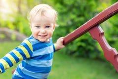 Portret van leuke schadelijke Kaukasische blonde babyjongen die houten leuning houden die trap beklimmen bij openluchtbinnenplaat stock fotografie