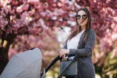 Portret van mammatribune met wandelwagen in het park Gelukkige jonge moeder die met baby lopen Achtergrond van roze boom stock fotografie