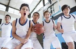 Portret van Mannelijk Middelbare schoolbasketbal Team Celebrating On Court royalty-vrije stock foto's