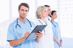 Portret van mannelijke arts het schrijven rapporten met erachter collega's Stock Fotografie