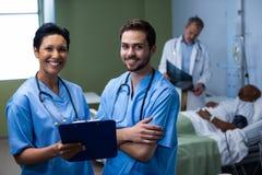 Portret van mannelijke en vrouwelijke verpleegster die zich in afdeling bevinden stock fotografie
