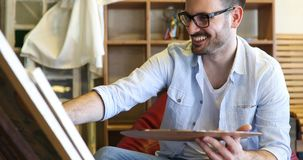 Portret van Mannelijke Kunstenaar Working On Painting in Studio stock fotografie