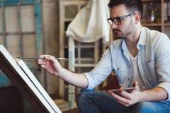 Portret van Mannelijke Kunstenaar Working On Painting in Studio royalty-vrije stock afbeeldingen