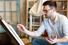 Portret van Mannelijke Kunstenaar Working On Painting in Studio stock foto's