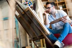 Portret van Mannelijke Kunstenaar Working On Painting in Studio stock afbeelding