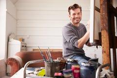 Portret van Mannelijke Kunstenaar Working On Painting in Studio royalty-vrije stock fotografie