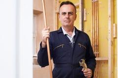 Portret van Mannelijke Loodgieter Working In House royalty-vrije stock afbeeldingen