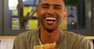 Portret van mannelijke uitvoerend hebbend hamburger 4k stock footage