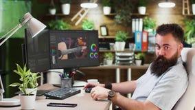 Portret van mannelijke videoredacteur of colorist die in comfortabel en modieus bureau werken stock video