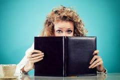 Portret van meisje achter boek Stock Afbeeldingen
