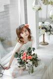 Portret van meisje het sitiing op witte houten vensterbank met groot licht venster stock foto's