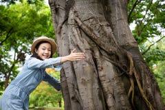 Portret van meisje in hoed met het glimlachen, het koesteren van grote boomboomstam en het bekijken camera in openluchtpark, Azia stock afbeelding