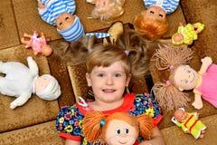 Portret van meisje (kind, jong geitje) met poppen op het tapijt Stock Foto