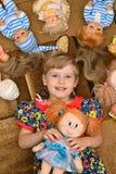 Portret van meisje (kind, jong geitje) met poppen op het tapijt Stock Foto's