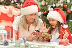Portret van meisje met grootmoeder het voorbereidingen treffen voor Kerstmis royalty-vrije stock afbeeldingen