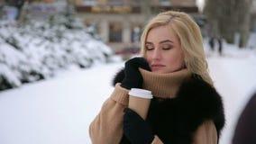 Portret van meisje met kop van koffie in sneeuwpark stock videobeelden