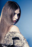 Portret van meisje met lang haar Jonge vrouw in bontjas op blauw Royalty-vrije Stock Foto