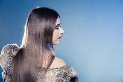 Portret van meisje met lang haar Jonge vrouw in bontjas op blauw Royalty-vrije Stock Foto's