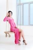 Portret van meisje in roze kledingszitting op schommeling Royalty-vrije Stock Foto's