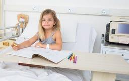 Portret van meisjes kleurend boek in het ziekenhuis Stock Foto's