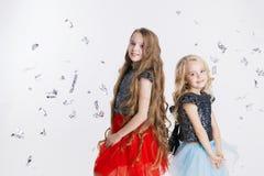 Portret van meisjes met krullend kapsel die zich op de vakantiepartij bevinden in kleding met lovertjes Conceptenviering Royalty-vrije Stock Afbeeldingen