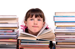 Portret van meisjeszitting onder stapels boeken Stock Fotografie