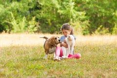 Portret van meisjeszitting op een grasrijke grond samen met haar huisdieren stock afbeelding