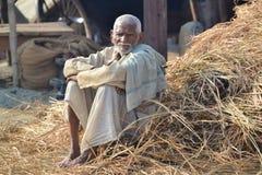 Portret van mensenzitting in stro, in Kumbh Mela Festival, Allahabad, India 2013 Stock Fotografie