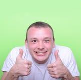 Portret van met de grappige duimen van de uitdrukkingsholding omhoog tegen gree Royalty-vrije Stock Foto's