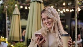 Portret van modieus jong leuk glimlachend meisje die moderne smartphone met behulp van terwijl het lopen in de stad Dame het type stock video