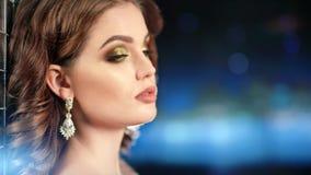 Portret van modieus model met mooi samenstelling en avondkapsel bij blauwe bokehachtergrond stock videobeelden