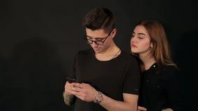 Portret van modieus paar in liefde met telefoons in handen op zwarte achtergrond stock footage