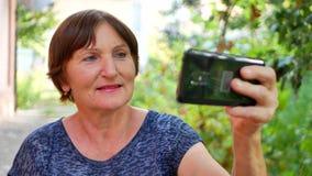 Portret van modieuze hogere vrouw gebruikend zwarte slimme telefoon en doend selfie stock videobeelden