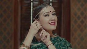 Portret van modieuze Indische vrouw die oorringen zetten stock videobeelden