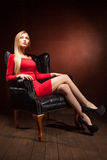 Portret van modieuze modelzitting in leunstoel Stock Fotografie
