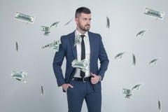 Portret van modieuze zakenman met dalende dollarbankbiljetten op grijze achtergrond gekleed in een kostuum met een modieus kapsel stock afbeeldingen