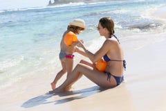Portret van moeder die haar dochter onderwijzen om op het strand te zwemmen royalty-vrije stock foto's