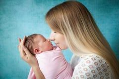 Portret van moeder die haar pasgeboren babymeisje koesteren stock fotografie