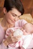 Portret van Moeder die Pasgeboren Baby thuis voedt stock fotografie