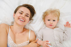 Portret van moeder en baby die in bed leggen Stock Fotografie
