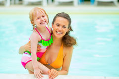 Portret van moeder en babymeisje in zwembad stock foto