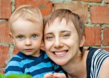 Portret van moeder met zoon bij bakstenen muur Stock Foto's
