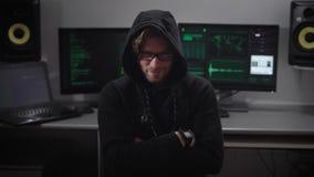Portret van moedwillige hakker die met een kap belangrijk gegevensbestand van netwerk downloaden De mens barstte firewall om te b stock footage